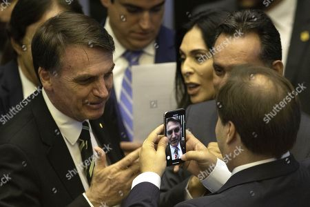 The president of the Chamber of Deputies of Brazil, Rodrigo Maia (R), records on video Brazil's President-elect Jair Bolsonaro (R) during Brazilian Parliament session to mark 30th anniversary of the Brazilian Constitution, in Brasilia, Brazil, 06 November 2018. Brazil's President-elect Jair Bolsonaro told lawmakers in Parliament the only goal for his government after he is sworn in on 01 January would be the Constitution.