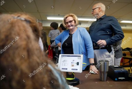 Incumbent Sen. Claire McCaskill, D-Mo., checks in with an election official alongside her husband, Joseph Shepard, right, before casting their ballots, in Kirkwood, Mo