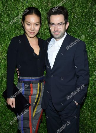 Ji Oh, left, and guest attend the 15th annual CFDA / Vogue Fashion Fund event at the Brooklyn Navy Yard, in New York