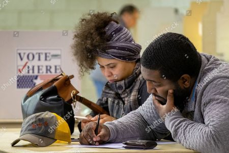 Jawanza Thompson (R) casts his ballot with his wife Shandell Thompson in the 2018 mid-term general election at Johnson-Wabash Elementary School in Ferguson, Missouri, USA, 06 November 2018. Missouri voters are selecting between incumbent US Senator Claire McCaskill, a Democrat, and Missouri Attorney General Josh Hawley, a Republican, to represent the state in the US Senate.