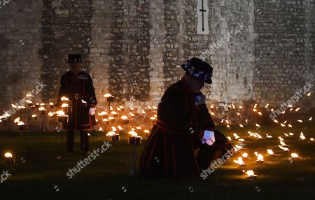 Yeomen Warders stands amongst thousands of torches at the Tower of London to commemorate the centenary of Armistice Day in London, Britain, 06 November 2018. This November, as the nation commemorates the centenary of the end of the First World War, a new installation at the Tower of London,called 'Beyond the Deepening Shadow', is now displayed. The Tower Remembers, will fill the moat with thousands of individual flames; a public act of remembrance for the lives of the fallen, honouring their sacrifice. The installation will run from 4 ? 11 November, for eight nights up to and including Armistice day 2018. Commissioned and produced by Historic Royal Palaces, this new light and sound installation brings together a talented creative team, including designer Tom Piper, Sound Artist and Composer Mira Calix, Lighting Designer Phil Supple and fire expert Mike Jones.