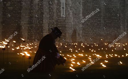 A Yeomen Warder kneels amongst thousands of torches at the Tower of London to commemorate the centenary of Armistice Day in London, Britain, 06 November 2018. This November, as the nation commemorates the centenary of the end of the First World War, a new installation at the Tower of London,called 'Beyond the Deepening Shadow', is now displayed. The Tower Remembers, will fill the moat with thousands of individual flames; a public act of remembrance for the lives of the fallen, honouring their sacrifice. The installation will run from 4 ? 11 November, for eight nights up to and including Armistice day 2018. Commissioned and produced by Historic Royal Palaces, this new light and sound installation brings together a talented creative team, including designer Tom Piper, Sound Artist and Composer Mira Calix, Lighting Designer Phil Supple and fire expert Mike Jones.