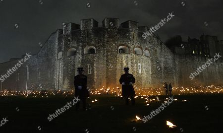 Yeomen Warders stand amongst thousands of torches at the Tower of London to commemorate the centenary of Armistice Day in London, Britain, 06 November 2018. This November, as the nation commemorates the centenary of the end of the First World War, a new installation at the Tower of London,called 'Beyond the Deepening Shadow', is now displayed. The Tower Remembers, will fill the moat with thousands of individual flames; a public act of remembrance for the lives of the fallen, honouring their sacrifice. The installation will run from 4 ? 11 November, for eight nights up to and including Armistice day 2018. Commissioned and produced by Historic Royal Palaces, this new light and sound installation brings together a talented creative team, including designer Tom Piper, Sound Artist and Composer Mira Calix, Lighting Designer Phil Supple and fire expert Mike Jones.