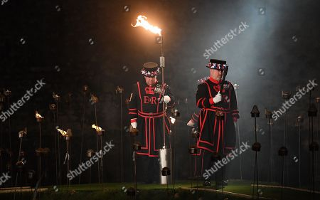 Yeomen Warders prepare to light thousands of torches at the Tower of London to commemorate the centenary of Armistice Day in London, Britain, 06 November 2018. This November, as the nation commemorates the centenary of the end of the First World War, a new installation at the Tower of London,called 'Beyond the Deepening Shadow', is now displayed. The Tower Remembers, will fill the moat with thousands of individual flames; a public act of remembrance for the lives of the fallen, honouring their sacrifice. The installation will run from 4 ? 11 November, for eight nights up to and including Armistice day 2018. Commissioned and produced by Historic Royal Palaces, this new light and sound installation brings together a talented creative team, including designer Tom Piper, Sound Artist and Composer Mira Calix, Lighting Designer Phil Supple and fire expert Mike Jones.