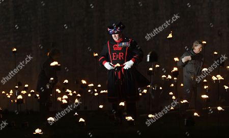 A Yeomen Warder walks amongst thousands of torches at the Tower of London to commemorate the centenary of Armistice Day in London, Britain, 06 November 2018. This November, as the nation commemorates the centenary of the end of the First World War, a new installation at the Tower of London,called 'Beyond the Deepening Shadow', is now displayed. The Tower Remembers, will fill the moat with thousands of individual flames; a public act of remembrance for the lives of the fallen, honouring their sacrifice. The installation will run from 4 ? 11 November, for eight nights up to and including Armistice day 2018. Commissioned and produced by Historic Royal Palaces, this new light and sound installation brings together a talented creative team, including designer Tom Piper, Sound Artist and Composer Mira Calix, Lighting Designer Phil Supple and fire expert Mike Jones.