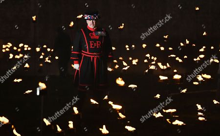 A Yeomen Warder stands amongst thousands of torches at the Tower of London to commemorate the centenary of Armistice Day in London, Britain, 06 November 2018. This November, as the nation commemorates the centenary of the end of the First World War, a new installation at the Tower of London,called 'Beyond the Deepening Shadow', is now displayed. The Tower Remembers, will fill the moat with thousands of individual flames; a public act of remembrance for the lives of the fallen, honouring their sacrifice. The installation will run from 4 ? 11 November, for eight nights up to and including Armistice day 2018. Commissioned and produced by Historic Royal Palaces, this new light and sound installation brings together a talented creative team, including designer Tom Piper, Sound Artist and Composer Mira Calix, Lighting Designer Phil Supple and fire expert Mike Jones.