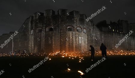 Stock Image of Thousands of torches in the dry moat around the Tower of London to commemorate the centenary of Armistice Day in London, Britain, 06 November 2018. This November, as the nation commemorates the centenary of the end of the First World War, a new installation at the Tower of London,called 'Beyond the Deepening Shadow', is now displayed. The Tower Remembers, will fill the moat with thousands of individual flames; a public act of remembrance for the lives of the fallen, honouring their sacrifice. The installation will run from 4 ? 11 November, for eight nights up to and including Armistice day 2018. Commissioned and produced by Historic Royal Palaces, this new light and sound installation brings together a talented creative team, including designer Tom Piper, Sound Artist and Composer Mira Calix, Lighting Designer Phil Supple and fire expert Mike Jones.