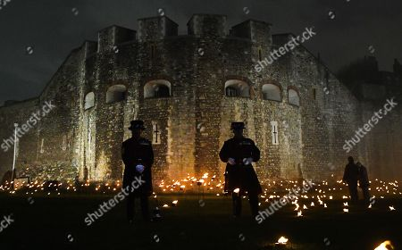 Stock Picture of Yeomen Warders stand amongst thousands of torches in the dry moat around the Tower of London to commemorate the centenary of Armistice Day in London, Britain, 06 November 2018. This November, as the nation commemorates the centenary of the end of the First World War, a new installation at the Tower of London,called 'Beyond the Deepening Shadow', is now displayed. The Tower Remembers, will fill the moat with thousands of individual flames; a public act of remembrance for the lives of the fallen, honouring their sacrifice. The installation will run from 4 ? 11 November, for eight nights up to and including Armistice day 2018. Commissioned and produced by Historic Royal Palaces, this new light and sound installation brings together a talented creative team, including designer Tom Piper, Sound Artist and Composer Mira Calix, Lighting Designer Phil Supple and fire expert Mike Jones.