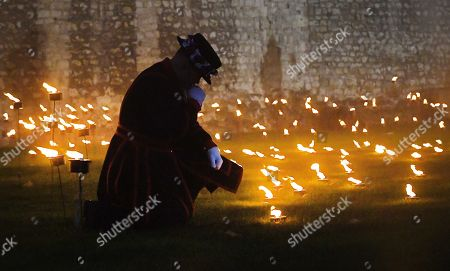 A Yeomen Warder kneels amongst thousands of torches in the dry moat around the Tower of London to commemorate the centenary of Armistice Day in London, Britain, 06 November 2018. This November, as the nation commemorates the centenary of the end of the First World War, a new installation at the Tower of London,called 'Beyond the Deepening Shadow', is now displayed. The Tower Remembers, will fill the moat with thousands of individual flames; a public act of remembrance for the lives of the fallen, honouring their sacrifice. The installation will run from 4 ? 11 November, for eight nights up to and including Armistice day 2018. Commissioned and produced by Historic Royal Palaces, this new light and sound installation brings together a talented creative team, including designer Tom Piper, Sound Artist and Composer Mira Calix, Lighting Designer Phil Supple and fire expert Mike Jones.