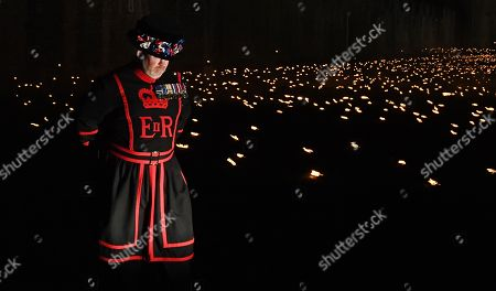 A Yeomen Warder stands amongst thousands of torches at the Tower of London to commemorate the centenary of Armistice Day in London, Britain, 06 November 2018. This November, as the nation commemorates the centenary of the end of the First World War, a new installation at the Tower of London, called 'Beyond the Deepening Shadow', is now displayed. The Tower Remembers will fill the moat with thousands of individual flames, a public act of remembrance for the lives of the fallen, honouring their sacrifice. The installation will run from 4 to 11 November, for eight nights up to and including Armistice day 2018. Commissioned and produced by Historic Royal Palaces, the light and sound installation brings together designer Tom Piper, Sound Artist and Composer Mira Calix, Lighting Designer Phil Supple and fire expert Mike Jones.