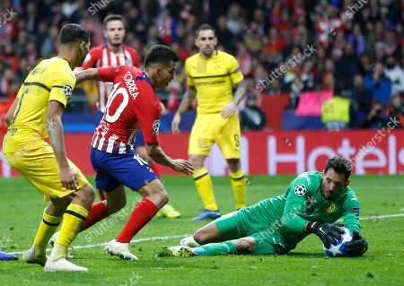 Borussia Dortmund's goalkeeper Roman Burki, right, makes a save during the Group A Champions League soccer match between Atletico Madrid and Borussia Dortmund at Wanda Metropolitano stadium in Madrid, Spain