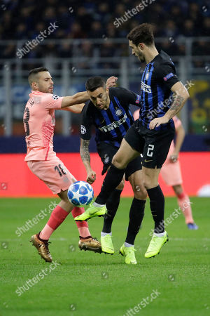 Barcelona defender Jordi Alba, left, fights for the ball against Inter midfielder Matias Vecino, center and Inter defender Sime Vrsaljko during the Champions League group B soccer match between Inter Milan and Barcelona at the San Siro stadium in Milan, Italy