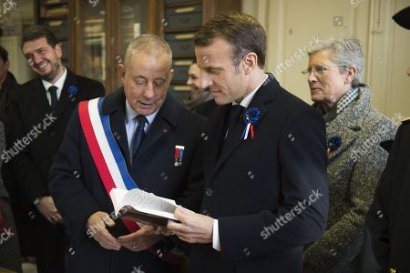 French President Emmanuel Macron (c) and Mayor Xavier Pierson (L) attend a meeting to commemorate French author Maurice Genevoix (1890-1980) at the city hall