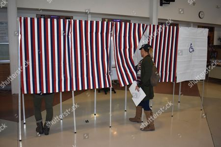 A voter enters a voting booth at Laurel High School, in Laurel, Mont. (AP Photo/Matthew Brown