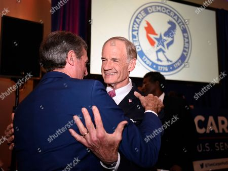 Stock Picture of Incumbent Sen. Tom Carper, D-Del., right, embraces Delaware Gov. John Carney at an election night party, in Wilmington, Del. Carper has been re-elected to a fourth term