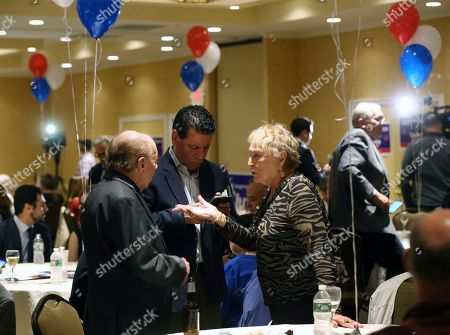 People talk in small groups during an election watch party for Tom MacArthur, the Republican candidate in New Jersey's third Congressional District, will not make an appearance, in Toms River, N.J. MacArthur, the Republican incumbent is facing Democrat Andy Kim in New Jersey's third Congressional District