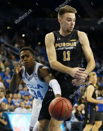Fort Wayne forward Dylan Carl, right, and UCLA guard David Singleton, left, battle for the ball during the first half of an NCAA college basketball game, in Los Angeles