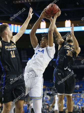 UCLA center Moses Brown, center, pulls in an offensive rebound between Fort Wayne forward Dylan Carl, left, and guard Kason Harrell, right, during the second half of an NCAA college basketball game, in Los Angeles. UCLA won 96-71