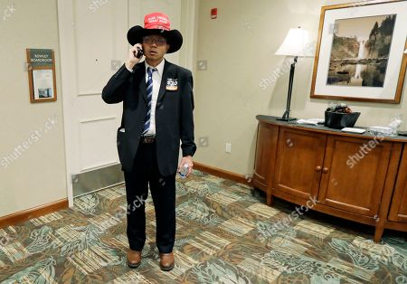 """John Wayne Lee, of Tacoma, Wash., wears a """"Make America Great Again"""" ball cap on top of his cowboy hat as he talks on his phone, at a Republican election-night gathering in Issaquah, Wash. Lee said he was at the event to support Dino Rossi, who was running for Washington's 8th district congressional seat, and other Republican candidates"""