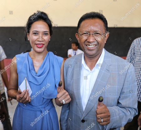Former Malagasy President and Presidential Elections candidate Hery Rajaonarimampianina and his wife look on after casting his ballot at a polling station in Antananarivo