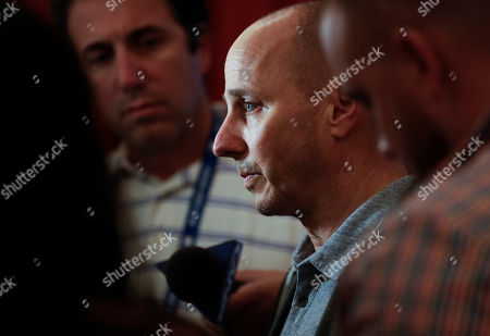 New York Yankees general manager Brian Cashman, center, speaks to reporters during the baseball GM meetings, in Carlsbad, Calif