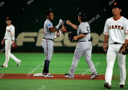 MLB All-Stars' Ronald Acuna Jr. (L) of the Atlanta Braves is congratulated by first base coach Hideki Matsui of the New York Yankees after hitting a second base hit in the first inning of the exhibition game between the Major League Baseball (MLB) Team and Yomiuri Giants at Tokyo Dome in Tokyo, Japan, 08 November 2018.