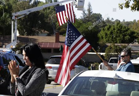 Kary Lloyd (L) prays and Kevin Kane (R) holds a US flag as the hearse carrying the body of Sargent Ron Helus passes by in Thousand Oaks, California, USA, 08 November 2018. 13 people were killed and several wounded in the mass shooting at the Borderline Bar & Grill. A sheriff's deputy, 11 attendees and the gunmen were killed.