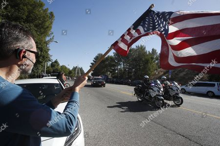 Stock Photo of Kevin Kane holds a US flag the motorcade accompanying the hearse carrying the body of Sergeant Ron Helus passes by in Thousand Oaks, California, USA, 08 November 2018. 13 people were killed and several wounded in the mass shooting at the Borderline Bar & Grill. A sheriff's deputy, 11 attendees and the gunmen were killed.