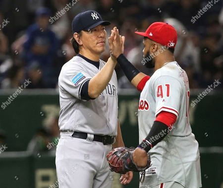 Stock Picture of Hideki Matsui, Carlos Santana. MLB All-Star first base coach Hideki Matsui, left, celebrates with first baseman Carlos Santana of the Philadelphia Phillies after beating the Yomiuri Giants 9-6 in their exhibition baseball game at Tokyo Dome in Tokyo
