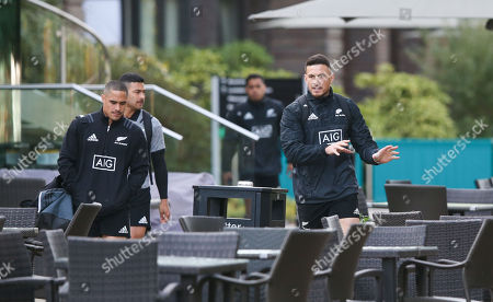 Sonny Bill Williams New Zealand All Blacks swerves the tables and chairs on his way to training with Aaron Smith (L)