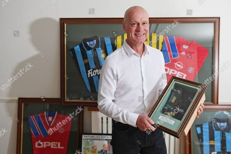 Stock Image of Jeremy Goss with his old boots and football shirts