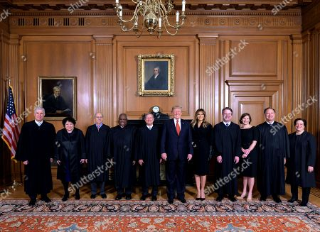 In this image provided by the Supreme Court, President Donald Trump poses for a photo with Associate Justice Brett Kavanaugh in the Justices' Conference Room before a investiture ceremony, at the Supreme Court in Washington. From left are, Associate Justices Neil Gorsuch, Sonia Sotomayor, Stephen Breyer, Clarence Thomas, Chief Justice John Roberts, Jr., President Donald Trump, first lady Melania Trump, Associate Justice Brett Kavanaugh, Ashley Kavanaugh, and Associate Justices Samuel Alito, Jr. and Elena Kagan
