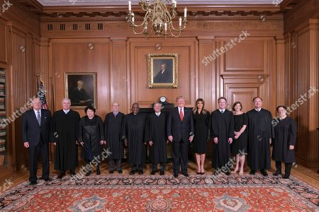 In this image provided by the Supreme Court, President Donald Trump poses for a photo with Associate Justice Brett Kavanaugh in the Justices' Conference Room before a investiture ceremony, at the Supreme Court in Washington. From left are, retired Justice Anthony Kennedy, Associate Justices Neil Gorsuch, Sonia Sotomayor, Stephen Breyer, Clarence Thomas, Chief Justice John Roberts, Jr., President Donald Trump, first lady Melania Trump, Associate Justice Brett Kavanaugh, Ashley Kavanaugh, and Associate Justices Samuel Alito, Jr. and Elena Kagan