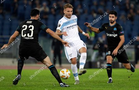 From left, Marseille's Adil Rami, Lazio's Ciro Immobile and Marseille's Morgan Sanson go for the ball during a Europa League, Group H soccer match between Lazio and Marseille, at Rome's Olympic stadium