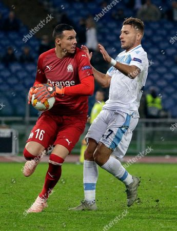 Stock Photo of Marseille's goalkeeper Yohann Pele grabs the ball ahead of Lazio's Ciro Immobile during a Europa League, Group H soccer match between Lazio and Marseille, at Rome's Olympic stadium