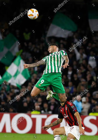 Betis' Toni Sanabria jumps for the ball against AC Milan's Riccardo Montolivo during the Europa League, Group F soccer match between AC Milan and Betis, at the Benito Villamarin Stadium in Seville, Spain
