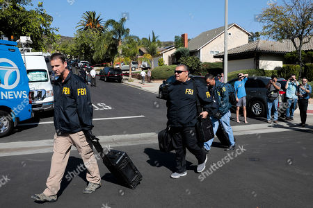 Stock Picture of FBI agents walk to their cars after collecting evidence at the house of shooting suspect David Ian Long after conducting a search in Newbury Park, Calif., on . Authorities said the former Marine opened fire at a country music bar in Southern California on Wednesday evening