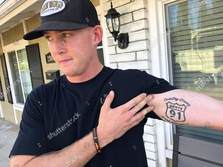 Brendan Kelly speaks with reporters outside his home, as he shows his Route 91 tattoo, in Thousand Oaks, Calif. Kelly, a Marine who was at Borderline Bar and Grill on Wednesday night, helped people get out after a gunman opened fire at the establishment. Kelly also survived the Las Vegas Route 91 Harvest Festival shooting in 2017