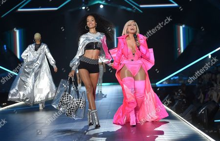 Melie Tiacoh, Bebe Rexha. Model Melie Tiacoh, left, walks the runway as singer Bebe Rexha performs during the 2018 Victoria's Secret Fashion Show at Pier 94, in New York
