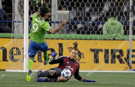 Seattle Sounders forward Raul Ruidiaz (9) has a shot deflected by Portland Timbers goalkeeper Jeff Attinella during the first half of the second leg of an MLS playoff soccer series, in Seattle