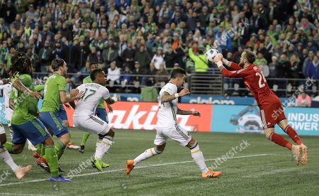 Seattle Sounders goalkeeper Stefan Frei, right, pushes out a ball as Portland Timbers defender Liam Ridgewell, second from left, closes in, during the first half of the second leg of an MLS soccer playoff series, in Seattle