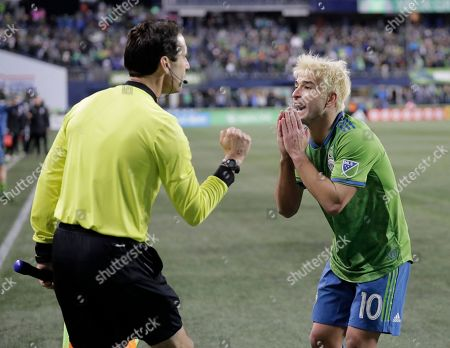 Seattle Sounders' Nicolas Lodeiro protests to an assistant referee after a goal scored by Sounders' Raul Ruidiaz was negated on a handball call against Ruidiaz during extra time in a second-leg MLS playoff soccer match against the Portland Timbers, in Seattle. The Sounders beat the Timbers 3-2 in the match, giving the aggregate series a 4-4 tie, but the Timbers proceeded to win the series in a penalty kick shootout