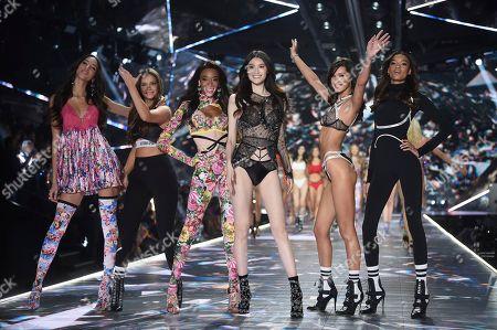 Yasmin Wijnaldum, Barbara Palvin, Winnie Harlow, Sui He, Bella Hadid, Lameka Fox. Models Yasmin Wijnaldum, left, Barbara Palvin, Winnie Harlow, Sui He, Bella Hadid and Lameka Fox walk the runway during the 2018 Victoria's Secret Fashion Show at Pier 94, in New York