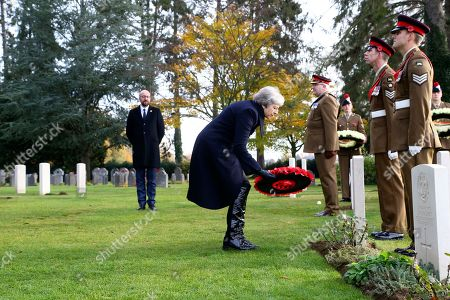 Britain's Prime Minister Theresa May lays a wreath at the grave of John Parr, the first British soldier to be killed in WWI in 1914, at the St Symphorien Military Cemetery in Mons, as Belgian Prime Minister Charles Michel looks on