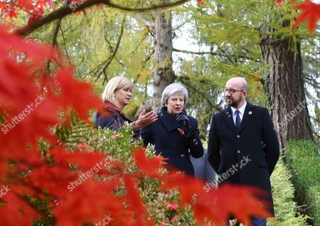 Britain's Prime Minister Theresa May, Belgian Prime Minister Charles Michel, right, and Liz Sweet, Director, External Relations, Western Europe Area, Commonwealth War Graves Commission, left, walk through the St Symphorien Military Cemetery in Mons, Belgium, where wreaths were placed at the graves of John Parr, the first British soldier to be killed in WWI in 1914, and George Ellison, the last British soldier to be killed before Armistice in 1918