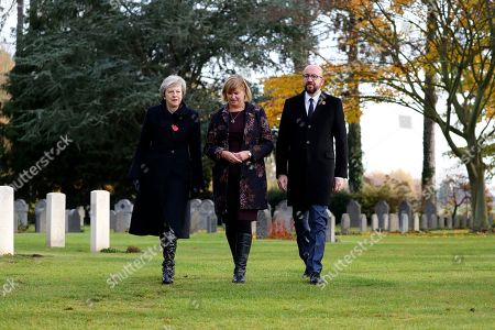 Britain's Prime Minister Theresa May, Belgian Prime Minister Charles Michel, right, and Liz Sweet, Director, External Relations, Western Europe Area, Commonwealth War Graves Commission, center, walk through the St Symphorien Military Cemetery in Mons, Belgium, where wreaths were placed at the graves of John Parr, the first British soldier to be killed in WWI in 1914, and George Ellison, the last British soldier to be killed before Armistice in 1918