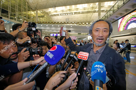 """Chinese dissident writer Ma Jian shows his passport to media after arriving Hong Kong international airport, . Hong Kong on Friday permitted dissident writer Ma to enter to attend a literary festival, even after an arts venue in the city canceled his appearance. Ma, whose novels frequently satirize China's communist leaders, told reporters he experienced nothing unusual while passing through passport control and that organizers were still lining-up a place for him to speak. """"The lecture will definitely happen. If there is a single Hong Kong person who is willing to listen, or a single reader who contacts me, I will be there,"""" Ma said"""