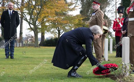 British Prime Minister Theresa May lays a wreath watched by Belgian Prime Minister Charles Michel (L) during the commemoration of the 100th anniversary of the end of the First World War at the Saint-Symphorien Military Cemetery, in Saint-Symphorien, Mons Belgium 09 November 2018. The cemetery at St. Symphorien was established by the German Army in August 1914 as the final resting place for British and German soldiers who were killed in the Battle of Mons. Among those buried here is Private John Parr of the Middlesex Regiment who was fatally wounded during an encounter with a German patrol two days before the battle, thus becoming the first British soldier to be killed in action on the Western Front. The cemetery remained in German hands until the end of the war and also contains the graves of Commonwealth and German soldiers who were killed in the final days of the conflict, including George Ellison of the Royal Irish Lancers and George Price of the Canadian Infantry. Ellison and Price were killed on Armistice Day 11 November 1918 and are believed to be the last Commonwealth casualties of the First World War. In total, there are 284 German and 230 Commonwealth casualties buried in this site.