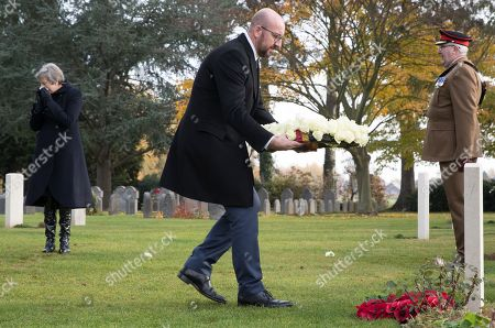 British Prime Minister Theresa May (L) as Belgian Prime Minister Charles Michel prepares to lay a wreath during the commemoration of the 100th anniversary of the end of the First World War at the Saint-Symphorien Military Cemetery, in Saint-Symphorien, Mons Belgium 09 November 2018. The cemetery at St. Symphorien was established by the German Army in August 1914 as the final resting place for British and German soldiers who were killed in the Battle of Mons. Among those buried here is Private John Parr of the Middlesex Regiment who was fatally wounded during an encounter with a German patrol two days before the battle, thus becoming the first British soldier to be killed in action on the Western Front. The cemetery remained in German hands until the end of the war and also contains the graves of Commonwealth and German soldiers who were killed in the final days of the conflict, including George Ellison of the Royal Irish Lancers and George Price of the Canadian Infantry. Ellison and Price were killed on Armistice Day 11 November 1918 and are believed to be the last Commonwealth casualties of the First World War. In total, there are 284 German and 230 Commonwealth casualties buried in this site.