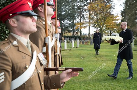 Stock Picture of British Prime Minister Theresa May (2-R) looks on as Belgian Prime Minister Charles Michel (R) prepares to lay a wreath during the commemoration of the 100th anniversary of the end of the First World War at the Saint-Symphorien Military Cemetery, in Saint-Symphorien, Mons Belgium 09 November 2018. The cemetery at St. Symphorien was established by the German Army in August 1914 as the final resting place for British and German soldiers who were killed in the Battle of Mons. Among those buried here is Private John Parr of the Middlesex Regiment who was fatally wounded during an encounter with a German patrol two days before the battle, thus becoming the first British soldier to be killed in action on the Western Front. The cemetery remained in German hands until the end of the war and also contains the graves of Commonwealth and German soldiers who were killed in the final days of the conflict, including George Ellison of the Royal Irish Lancers and George Price of the Canadian Infantry. Ellison and Price were killed on Armistice Day 11 November 1918 and are believed to be the last Commonwealth casualties of the First World War. In total, there are 284 German and 230 Commonwealth casualties buried in this site.